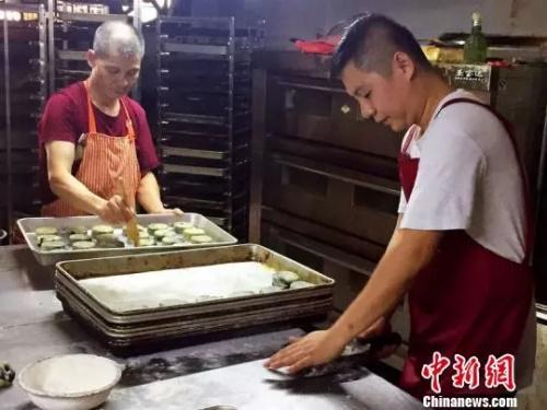陈立新与陈超雄父子在制作传统豆沙月饼 李晓春 摄