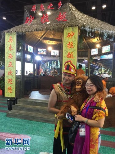 """9月14日,在广西南宁国际会展中心,观众在""""魅力之城""""之一的马来西亚砂拉越州展区前合影。新华网发 张茵摄"""