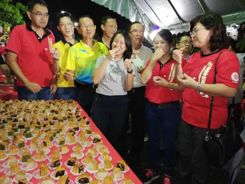 王丽丽(前左四)品尝月饼;其左后方为黄维忠。(马来西亚《星洲日报》)