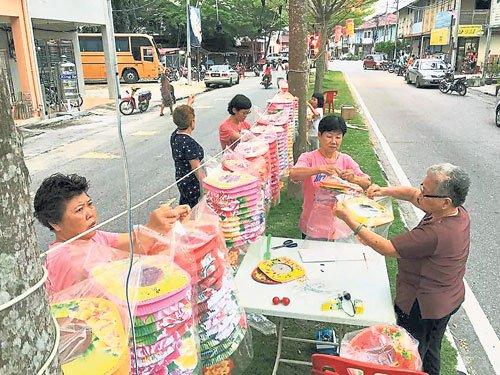 村民分工合作将透明的塑料袋倒套着纸制的灯笼,避免灯笼被雨淋湿或被曝晒损坏。(马来西亚《中国报》/村民提供照片)