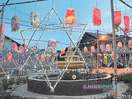 挂上巨型星星和灯笼的莫珍歪新村内的唯一交通圈,亮灯后分外抢眼。(马来西亚《中国报》/郭慧姗 摄)
