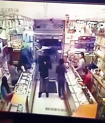 一名嫌犯鸣枪恐吓,另一人爬进柜台抢走珠宝。视频截图