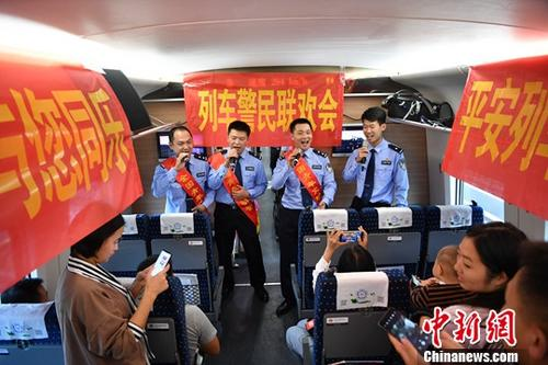"""9月19日,乘警们为旅客送上《敖包相会》《弯弯的月亮》等几首大家耳熟能详的歌曲。当日,在昆明开往上海的G1376次列车上,昆铁警方精心组织了一场""""中秋列车警民联欢会"""",为出行的旅客送上中秋节日祝福。<a target='_blank' href='http://www.chinanews.com/'>中新社</a>记者 刘冉阳 摄"""