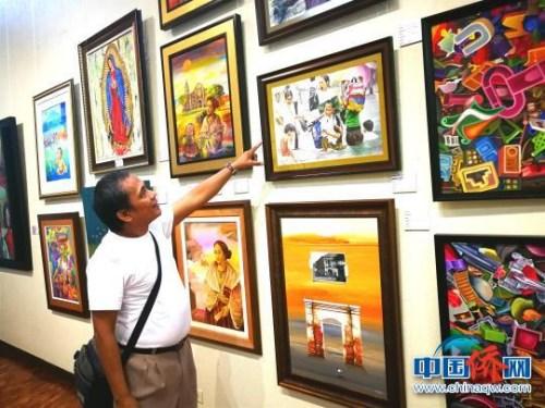 菲律宾画家向记者介绍自己的作品。 关向东 摄