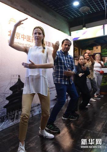 """资料图片:9月18日,外国友人在中国太极拳爱好者(左三)的指导下打太极拳。9月18日,由北京市旅游发展委员会主办的""""北京中医药健康旅游海外达人体验活动""""在北京举行,来自俄罗斯、西班牙、墨西哥、巴基斯坦等国的十余位外国友人来到北京前门大街,体验了太极拳、中医号脉、制作中药丸等中国传统文化项目。(新华社记者 任鹏飞 摄)"""