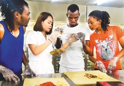 10月5日,非洲留学生在河北沧州吴桥县的一家中医馆体验中医抓药。   本报记者 史自强摄