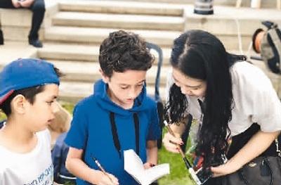 今年端午节,刘津巧(右)在当地的龙舟赛活动中为外国小朋友介绍中国书法。