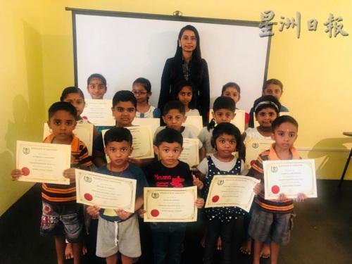 """在完成了一个阶段的学习后,孩童们开心地从普丽缇(后排中)手中接过""""毕业证书""""。(马来西亚《星洲日报》)"""