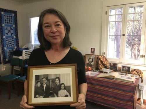 黄美华手捧父母生前照片,照片中小女孩是黄美华孩童时,华裔男童是她父母领养的,成为她的弟弟。(美国《世界日报》/启铬 摄)