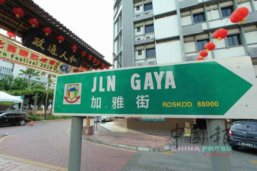 """资料图:加雅街牌楼前,设有""""加雅街""""中巫双语路牌。"""