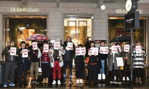 """当地时间21日晚,米兰华人手举""""Not Me""""标语,在D&G旗舰店门外发首无声抗议运动,曾数度与D&G配相符的男模刘星宇亦(左六)在其中。(欧洲时报记者夏晓彤摄)"""