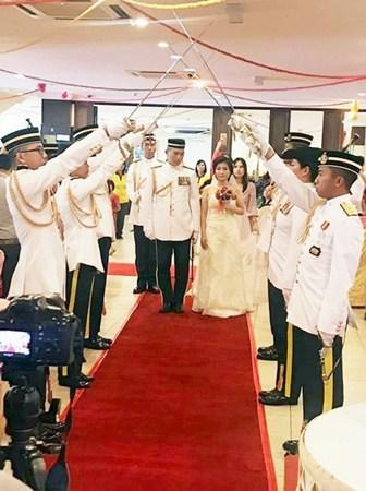 """6名军官面对面举剑形成""""剑门"""",一对新人走在红地毯缓缓进场。(马来西亚《星洲日报》)"""