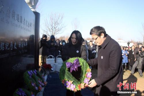 当地时间12月9日,由当地华侨华人筹资修建的南京大屠杀遇难者纪念碑在加拿大多伦多揭幕。这座由多伦多华人团体联合总会与加拿大中国洪门民治党多伦多支部共同发起修建的纪念碑坐落在大多伦多地区列治文山的爱恩墓园内,坐西朝东。图为加拿大华人国会议员谭耕(右)、关慧贞向纪念碑献花。中新社记者 余瑞冬 摄