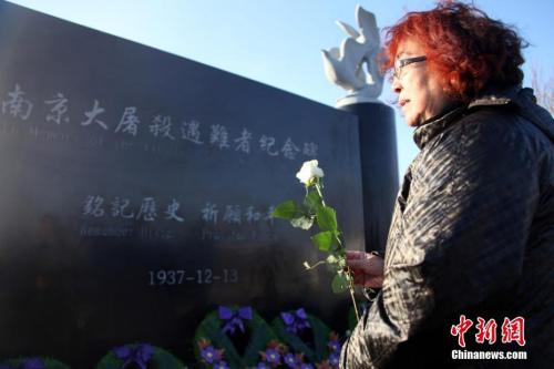 图为当地侨社代表向纪念碑献花。中新社记者 余瑞冬 摄