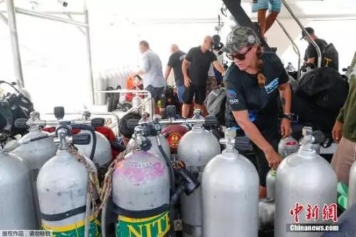 泰国普吉翻船事故搜救潜水员携带氧气罐准备救援。