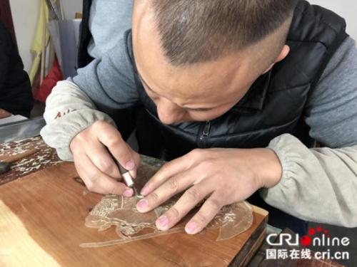 """皮影匠人用华州皮影独一无二的""""推皮走刀法""""雕刻。摄影:张捷"""