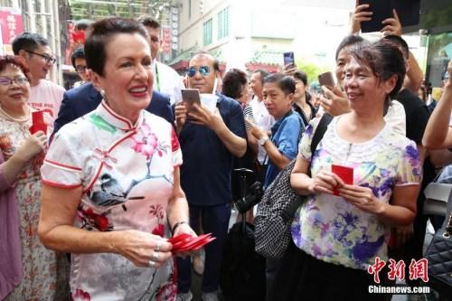 2月5日,中国农历新年大年初一,悉尼市长克罗芙·摩尔(左)到唐人街拜年,与商户和游人共庆中国新年。图为摩尔向游人派发利是红包。中新社记者 陶社兰 摄