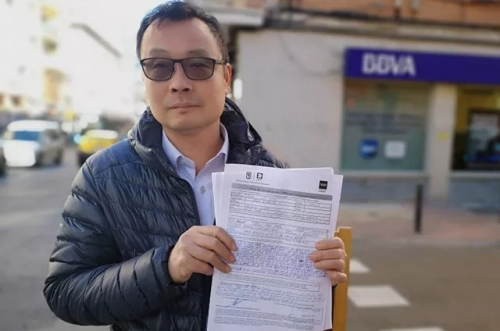 侨胞Enguan Chen在Usera一家BBVA营业厅门前向媒体展示了他的投诉单。(图片来源:《国家报》)