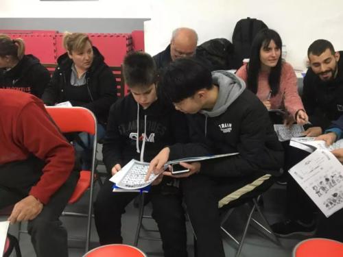 志愿者黄承辉(前排右一)辅导学员汉语拼音。(《欧洲时报》/苏珊娜 摄)