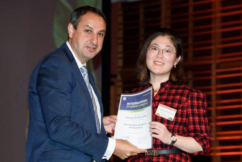 迪斯达(左)向中国留学生赵轶嵘(右)颁发「优秀学业奖」证书。