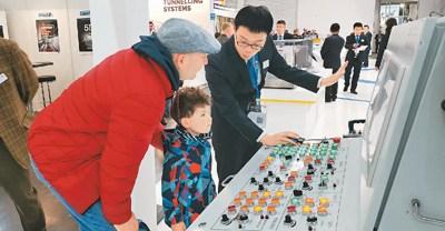 """在2019年德国""""宝马展""""中铁装备展区内,工作人员利用三维虚拟仿真操作系统向参观者讲解展出的盾构机原理和结构。"""