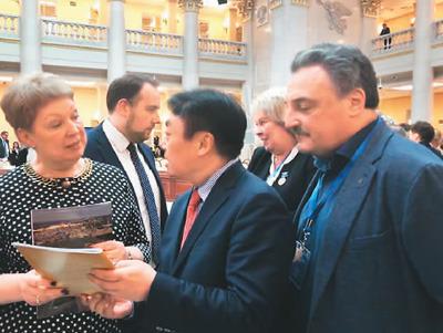 2019年3月,吴昊(中)在参加俄罗斯圣彼得堡国际教育论坛时,向俄罗斯教科部部长瓦西里耶娃女士(左)介绍『自己办的俄文杂志。