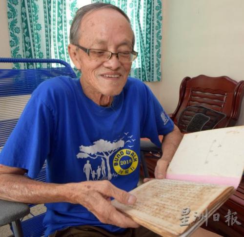 退休后的沈益辉,空闲时会拿出《桃李录》回味在课室与学生互动的日子。(图片来源:马来西亚《星洲日报》)