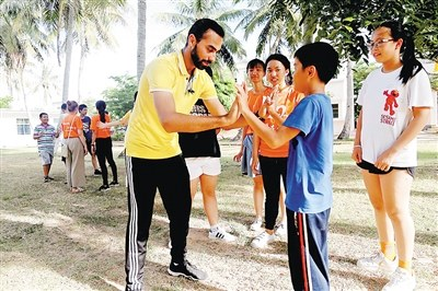 埃及大学生志愿者艾哈迈德与孩子们做游戏。 本报记者 袁宇 通讯员 杨一帆 摄