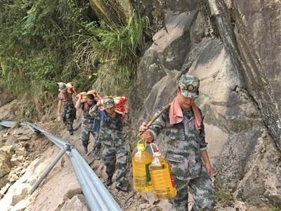 输送物资的小分队行走在塌方公路旁的陡峭山边。云岭乡供图