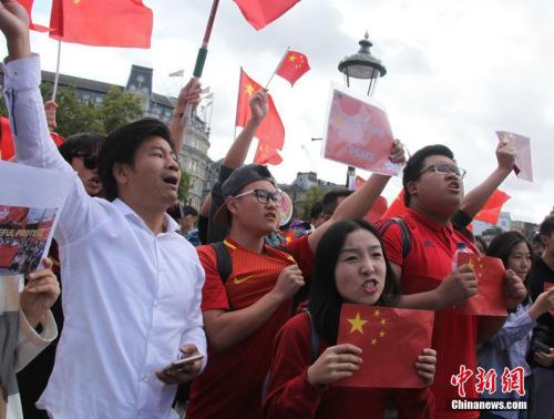 """8月17日,旅居英国的华人华侨、中国留学生300多人自发聚集在伦敦市中心特拉法加广场、议会广场,与""""乱港分子""""组织的示威游行队伍对峙。人们挥舞中国国旗,高唱中国国歌,高喊""""爱中国、爱香港""""""""反暴力、救香港""""口号,声浪阵阵压过""""乱港分子""""阵营。图为现场群情激昂的华人青年。<a target='_blank' href='http://www.chinanews.com/'>中新社</a>记者 张平 摄"""