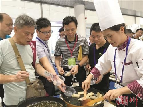 """在""""潮州馆""""内,由潮州菜师傅制作的潮州特色小食吸引了众多群众和�v采购商争相品尝。 本报记者 梁佳涛 摄"""