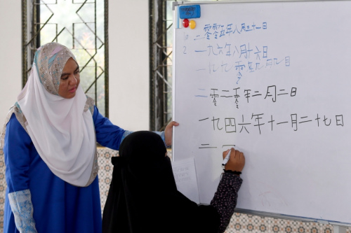 卢莱茵在课堂上教导学生用华文字写出日期。(马来西亚《星洲日报》/陈敬晖 摄)