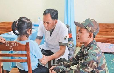 """图为""""和平列车""""医疗队队员正在老挝巴色市为当地民众做身体检查。 本报记者 孙广勇/摄"""