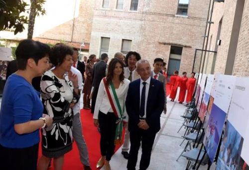 副总领事汪慧娟向意大利客人介绍图片展内容。(意大利欧联网)