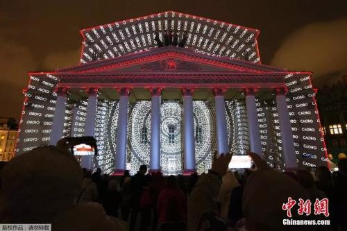 """资料图:当地时间2019年9月21日,俄罗斯莫斯科举办第九届""""光之环""""国际灯光节。人们在莫斯科大剧院前欣赏灯光秀表演。"""