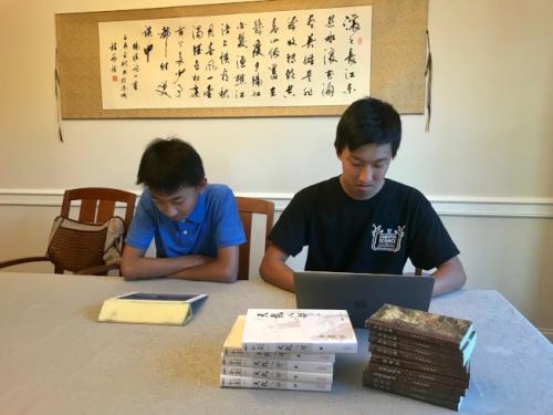 图为杨瑞盟(右)用笔记本电脑编程,杨海盟用iPad读标了拼音的金庸电子书。(美国《世界日报》记者王明心/拍摄)