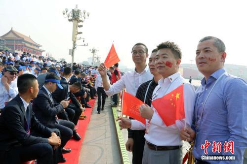 10月1日,庆祝中华人民共和国成立70周年大会在北京隆重举行。约2000名海外华侨华人在现场见证了历史时刻。他们表示,国庆庆典展现了中华民族的自信和威严,凝聚起了全球侨胞的心。图为来自巴布亚新几内亚的薛辉雄等在观礼台合影。<a target='_blank' href='http://www.chinanews.com/'>中新社</a>记者 任海霞 摄