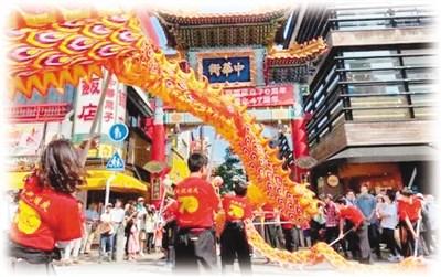10月1日,在日本横滨中华街上,当地华侨华人在举行舞龙表演。   图片来源:日本中文导报