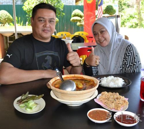"""来自玻璃市的阿斯玛里与妻子认为""""沙煲咖喱鲶鱼""""很赞。(马来西亚《星洲日报》/颜维陞 摄)"""
