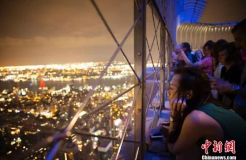 在纽约帝国大厦上观赏夜景的女性。<a target='_blank' href='http://www.chinanews.com/' _cke_saved_href='http://www.chinanews.com/'>中新社</a>记者 廖攀 摄