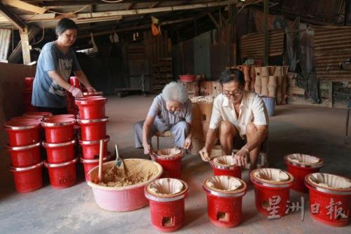 方家人将内炉叠到外炉里,以黄泥封住炉顶的空隙。(马来西亚《星洲日报》)