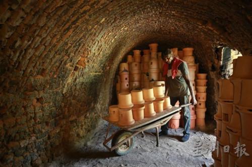 员工将一批晒透的外炉推入窑内。(马来西亚《星洲日报》)