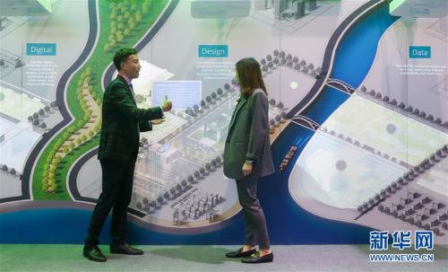 """11月6日,在第二届上海进博会服务贸易展区,德勤工作人员(左)向参观者介绍""""魔墙""""的功能。(新华社记者 丁汀 摄)"""