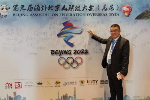 第三届海外北京人联谊大会主席、澳大利亚北京会会长高鹏在助力冬奥签名板上签名。