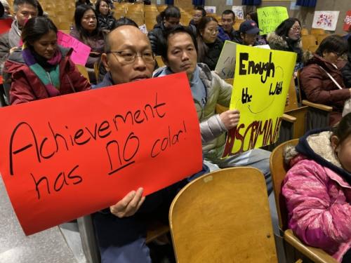 纽约上百名华裔家长手举抗议牌在会议现场。(美国《世界日报》/黄伊奕 摄)