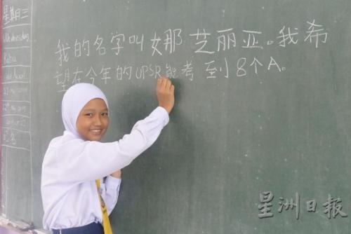 娜芝丽亚以工整的中文字体,在黑板上写下自己 的心愿。(来源:星洲日报)