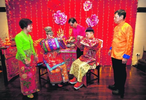 新郎的父亲李荣佳(右一)在给儿子操办婚礼时,特地前往马六甲重金礼聘传统婚礼礼仪师,而部分古董和珠宝是来自他个人及友人的收藏。多方奔走后,最终圆满举行了一场遵循传统习俗的婚礼。 (新加坡《联合早报》/梁麒麟 摄)