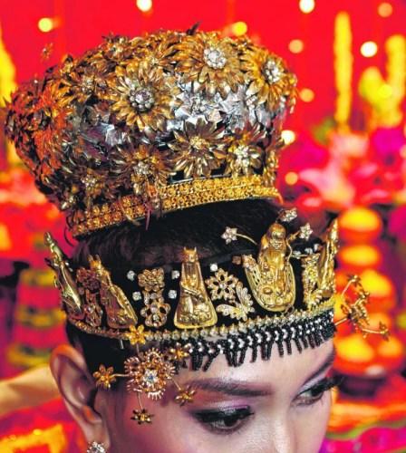 土生华人新娘头戴装饰珠宝的凤冠,特别之处是额前饰以八仙形象的金头套与花形镶钻金饰。 (新加坡《联合早报》/梁麒麟 摄)