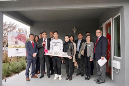 阿市市长Ross J. Maza(前排左二)将新屋钥匙交给阿市华裔居民Yi Pang(前排左三)与他的母亲张春芝(前排左四)。(美国《世界日报》记者陈开/摄 )