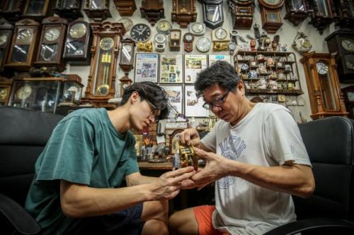 从中四开始学习修钟,林吉祥(左)大部分的童年都是与父亲林志光,在工作台前度过。